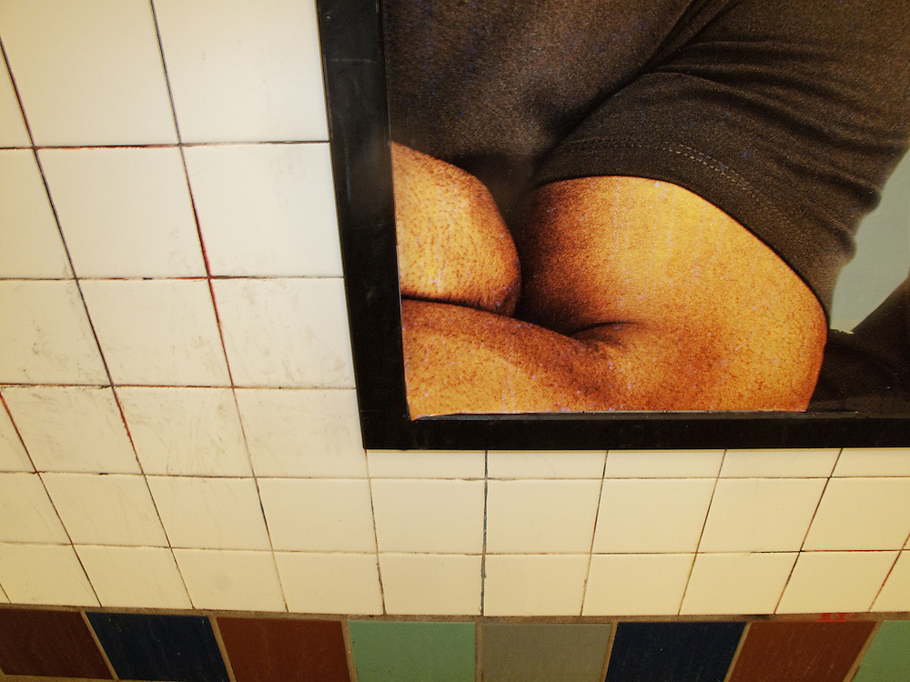 The large biceps of a man is seen in a poster on the white and color tile wall of a New York City subway platform.
