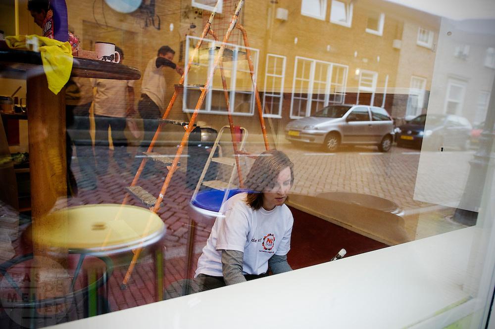 In het kader van het door het Oranjefonds bedachte vrijwilligersactie op 19 en 20 maart schilderen medewerkers van een verzekeringsmaatschappij het kantoor van de Utrechtse daklozenkrant Straatnieuws