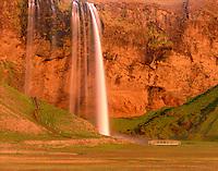 Seljalandfoss waterfall illuminated in the midnight sun, Iceland