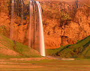 Seljalandfoss waterfall illuminated in the midnight sun, Iceland