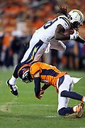 Los Angeles Chargers running back Melvin Gordon (28) gets upended by a defender as he catches a pass and runs for an 11 yard touchdown that ties the second quarter score at 7-7 during the 2017 NFL week 1 regular season football game against the Denver Broncos, Monday, Sept. 11, 2017 in Denver. The Broncos won the game 24-21. (©Paul Anthony Spinelli)