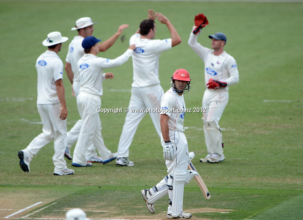 Canterbury's Dean Brownlie on his way back to the dressing room as Auckland players celebrate. Plunket Shield Cricket, Auckland Aces v Canterbury Wizards at Eden Park Outer Oval. Auckland on Sunday 16 December 2012. Photo: Andrew Cornaga/Photosport.co.nz