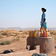 Nomadic Berber woman filling water bottles in the Sahara Desert, Morocco