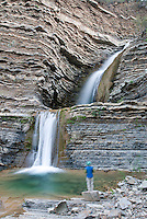 A hiker in front of Twin Falls in the Matilija Wilderness Area in Los Padres National Forest near Ojai, California.