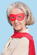 Portrait of senior woman wearing superhero costume against blue background