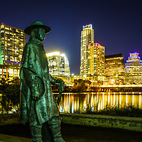 Stevie Ray Vaughan Memorial bronze statue with the Austin, Texas skyine at night along the Colorado River.