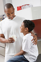 Father holding glass of milk, embracing son (7-9) indoors