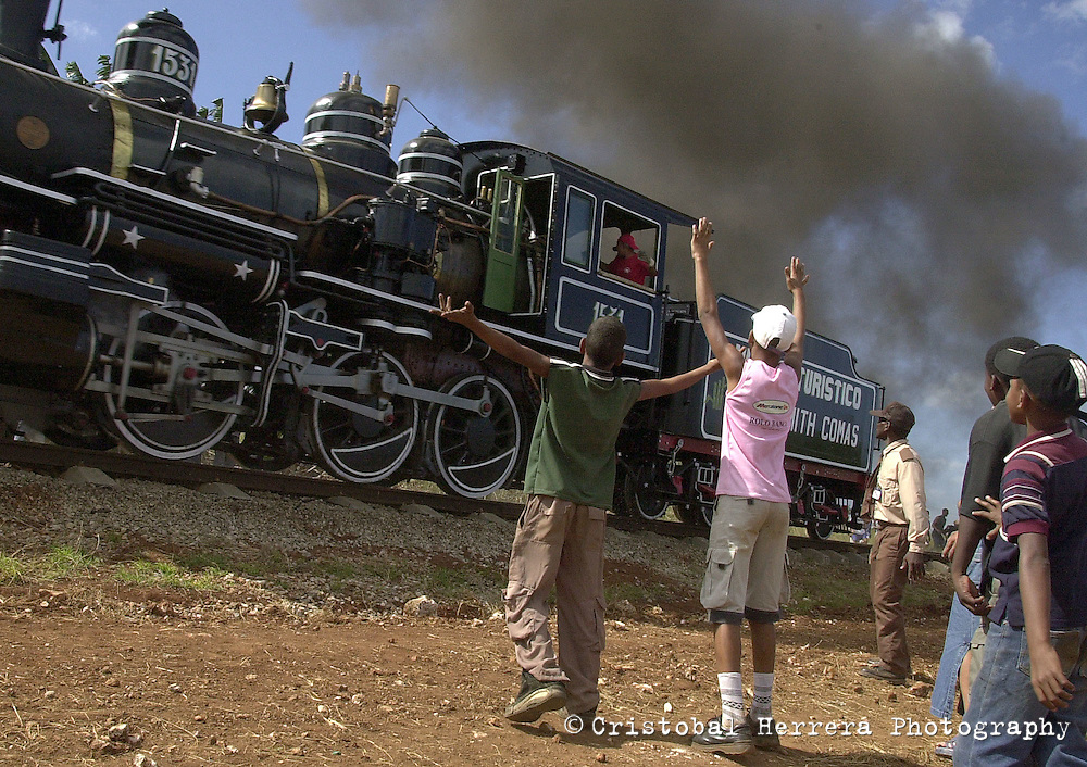 Steam locomotive crew, right, talk before starting the speed competition at the sugar factory of Cardenas city, about 150 km at East of Havana, Friday November 21, 2003, Cardenas, Cuba. Between November 20th and 30th, 2003, will be held in Cuba, the Steam International Festival, featuring tours throughout the country. In this festival participated railroad workers who drive the old steam engines, many of them still at service after nearly three centuries. (Photo/Cristobal Herrera)