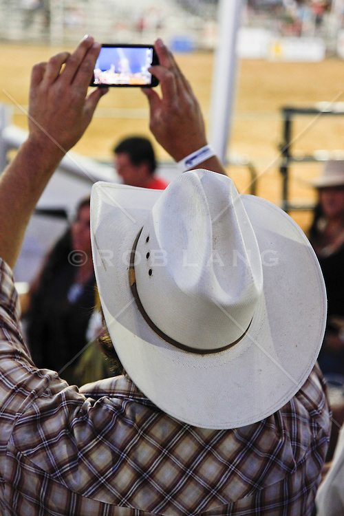 cowboy photographing at a rodeo