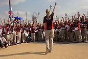 With the main stadium and the Orbit art tower behind, a choir of volunteer Games Makers sing for the entertainment of arriving spectators in the Olympic Park during the London 2012 Olympics. One of their number advertised in an Olympic newsletter for singers to join in resulting in 100 asking to join. Volunteers are called 'Games Makers', as they are helping to make the Games happen. Up to 70,000 Games Makers take on a wide variety of roles across the venues: from welcoming visitors; to transporting athletes; to helping out behind the scenes in the Technology team to make sure the results get displayed as quickly and accurately as possible. Games Makers come from a diverse range of communities and backgrounds, from across the UK and abroad. The vast majority are giving up at least 10 days to volunteer during the Games.
