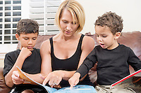 Mother reading book with two children