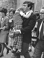 John McCabe carries his 6 year old daughter, Karen, at the funeral of his other daughter, Siobhan, on 12th August 1975 in Belfast, N Ireland. Siobhan died on 10th August 1975 from a ricochet bullet in gunfire between British soldiers and members of the Provisional IRA. The IRA attack would have been to mark the 4th anniversary of internment. 1974081201JMC.<br />