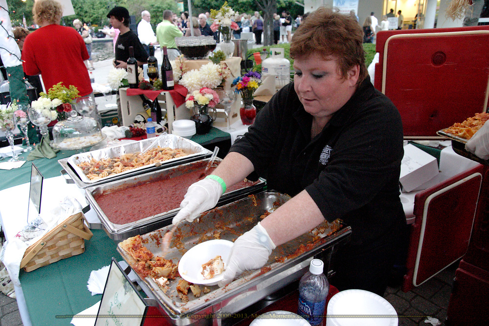 Getting the last samples out of a tray of lasagna before switching trays at the Spaghetti Warehouse booth during the 21st annual The Taste in the Lincoln Park Commons area at the Fraze Pavilion, Thursday, September 3, 2009.