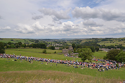 © Licensed to London News Pictures. 06/07/2014. Oxenhope nr Bradford, UK. 2nd Stage. The Tour de France peloton snakes its way up out of Oxenhope in Brontë country to scale the 3rd category climb of Oxenhope Moor before heading down to Hebden Bridge. The 7 man leading break had under 4 minutes lead. Photo credit : Ian Homer/LNP