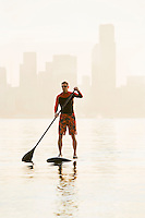 An athletic man paddling out on Elliott Bay early in the morning across from the downtown Seattle waterfront.