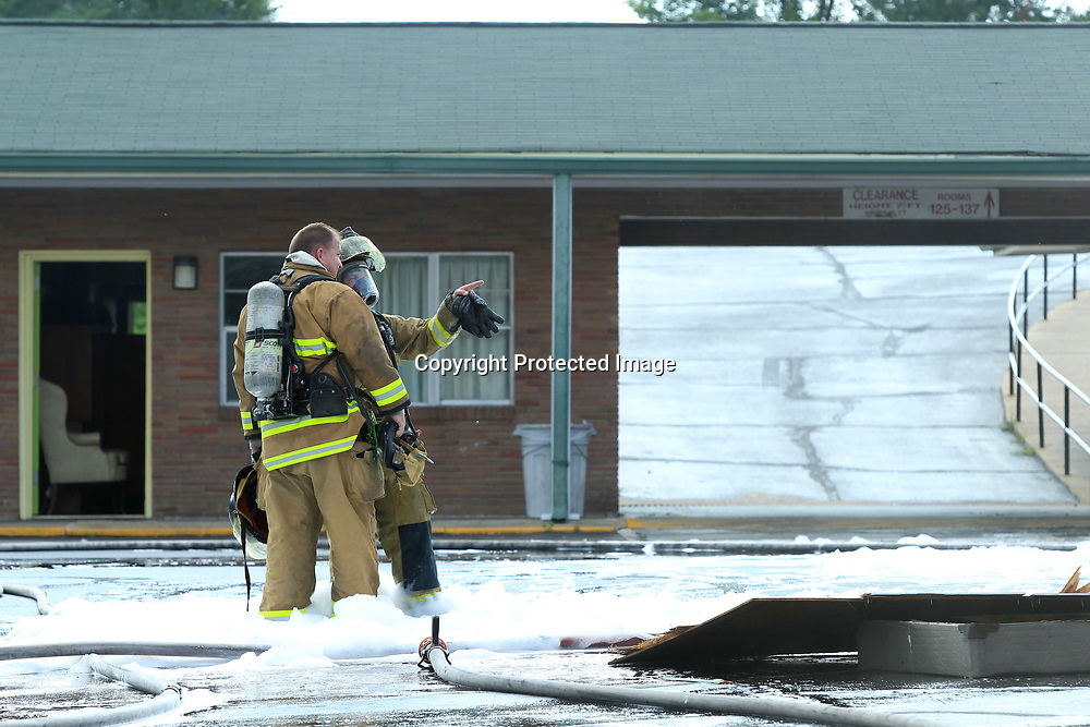 Two Tupelo firefighters talk while working with other firefighters as they put out  a fire at the Town House Motel on South Gloster Street Wednesday afternoon in Tupelo.