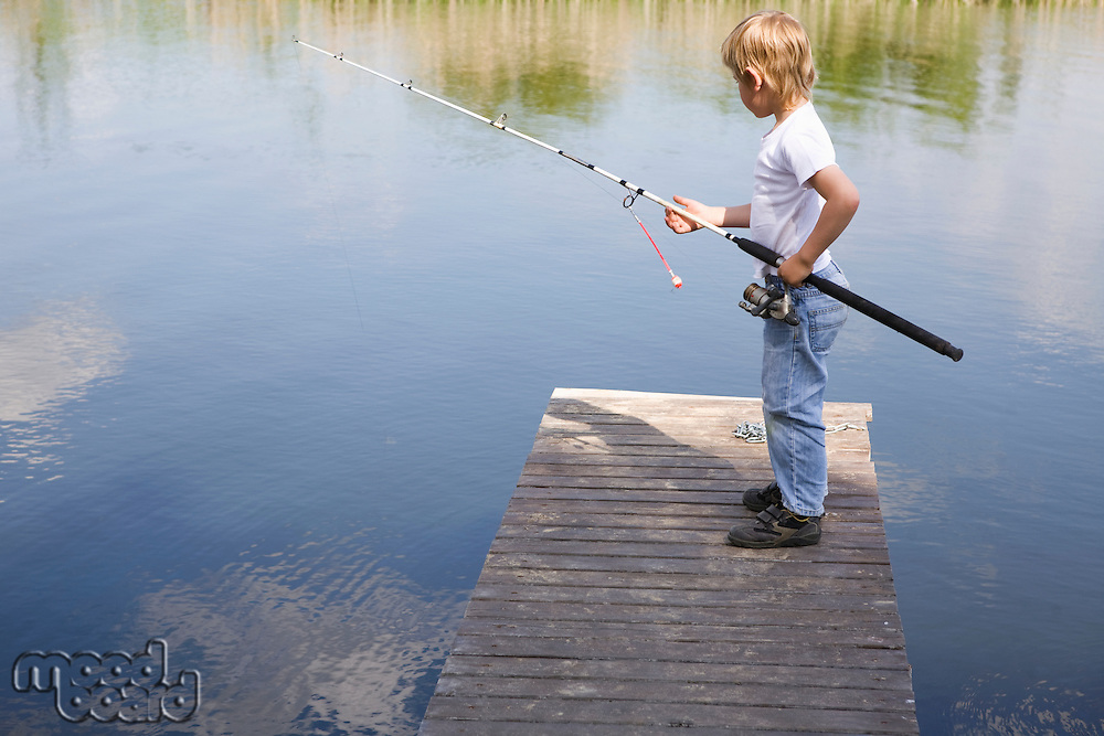 Boy fishing from jetty