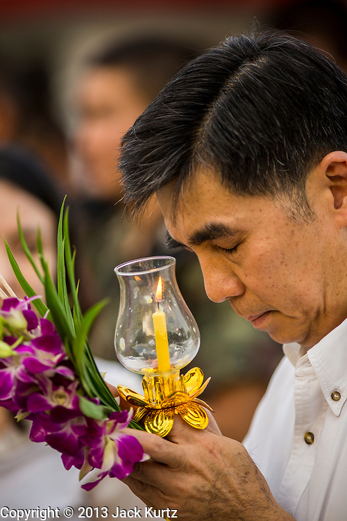 """25 FEBRUARY 2013 - BANGKOK, THAILAND:  A man prays at Wat Benchamabophit Dusitvanaram (popularly known as either Wat Bencha or the Marble Temple) on Makha Bucha Day. Makha Bucha is a Buddhist holiday celebrated in Myanmar (Burma), Thailand, Cambodia and Laos on the full moon day of the third lunar month (February 25 in 2013). The third lunar month is known in Thai is Makha. Bucha is a Thai word meaning """"to venerate"""" or """"to honor"""". Makha Bucha Day is for the veneration of Buddha and his teachings on the full moon day of the third lunar month. Makha Bucha Day marks the day that 1,250 Arahata spontaneously came to see the Buddha. The Buddha in turn laid down the principles his teachings. In Thailand, this teaching has been dubbed the 'Heart of Buddhism'.     PHOTO BY JACK KURTZ"""