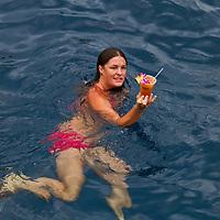 Woman enjoying Mai Tai in the tropical waters of Big Island Hawaii.