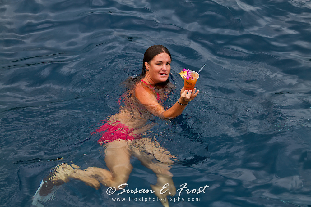 Woman enjoying Mai Tai in the tropical waters of Big Island Hawaii.