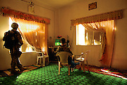 U.S. Army Spec. David Johnson stands guard near a window while his buddy, Spec. Kyle Laney, takes a break in front of the television, which is playing Iraqi cartoons, during a raid in Baqubah, Iraq, on April 2, 2007.