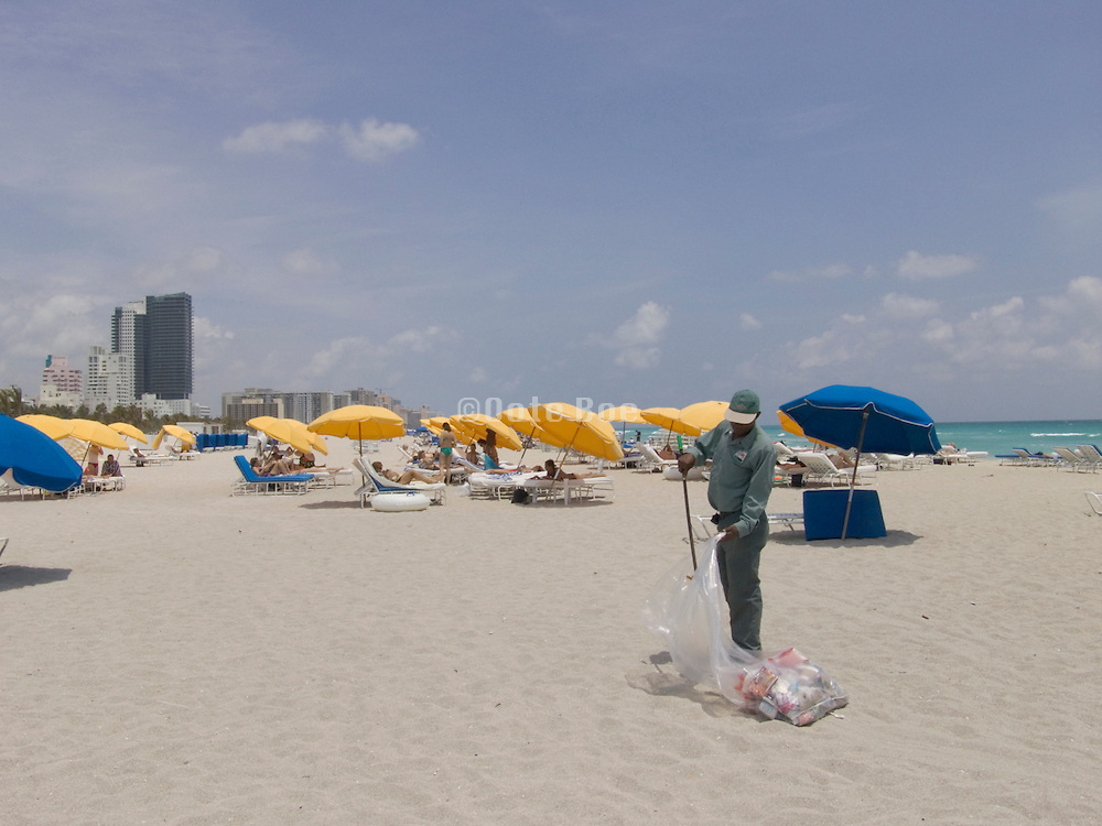 worker cleaning the beach of left behind garbage Miami USA