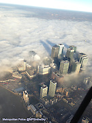 """Stunning Images of London covered in Fog<br /> <br /> It was foggy across London today but a specialist Metropolitan Police team rose above the gloom and had a unique view of the city. The MPS Air Support Unit (ASU) was up in the sky today, Wednesday 11 December, despite the weather having an impact on airports in and around London.<br /> <br /> One stunning image of Canary Wharf - towering above the fog in the low afternoon sun - has been shared throughout the world after being posted on their Twitter account @MPSintheSky. Taken on an iPhone by the crew whilst travelling to a job; the snap has been embraced by their followers and new fans alike.<br /> <br /> Captain John Roberts was piloting the MPS helicopter this afternoon - call sign India 99 - he said: """"Fog is a challenging condition to fly around, but once above it we were able to carry out our normal taskings. We only take photos on the way to or from a job and it has no negative impact on our policing purpose - supporting officers on the ground and keeping Londoners safe.<br /> <br /> """"We set up our Twitter account @MPSinthesky to engage with Londoners as we know that the helicopter can be loud sometimes and we like to explain what we're up to, especially at night - but it's developed into a unique perspective of London and we're proud to be able to provide great images of our iconic city!""""<br /> <br /> The MPS Air Support Unit has established itself as one of the leading police Twitter accounts in the UK. Originally set up to reduce noise complaints, the account continues to grow in popularity and with regular images of iconic landmarks and events it is easy to understand why.<br /> ©MPSintheSky/Exclusivepix"""