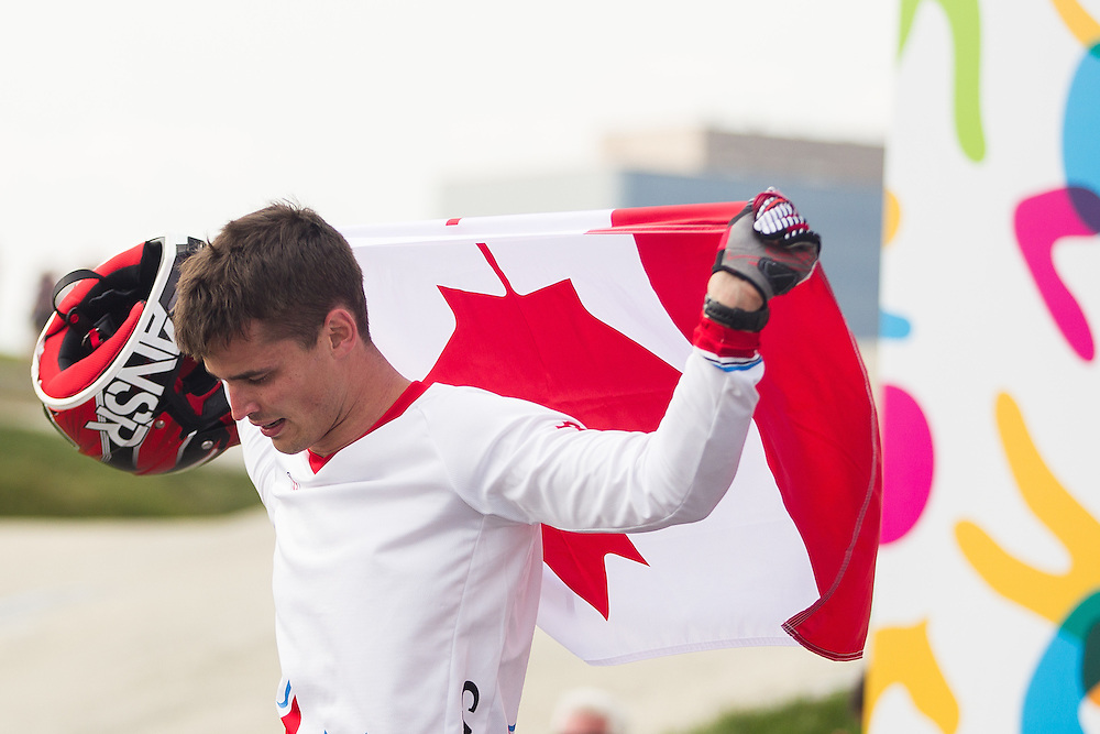 Gold medalist Tory Nyhaug of Canada walks with the Canadian flag after winning the BMX competition at the 2015 Pan American Games in Toronto, Canada July 11,  2015.  AFP PHOTO/GEOFF ROBINS