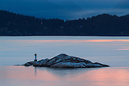One of the Grebe Islets in Howe Sound.  Photographed at sunset from Juniper Point at Lighthouse Park in West Vancouver, British Columbia, Canada. Bowen Island is in the background.