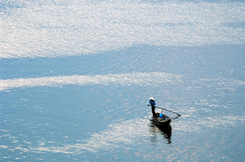 Woman rows across the Perfume River in her canoe, Hue, Vietnam