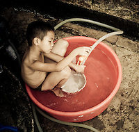 A young boy bathes with his toy horse in a small tub behind his parent's guest house in Luang Prabang, Laos, Vietnam, Southeast Asia, May, 2008.