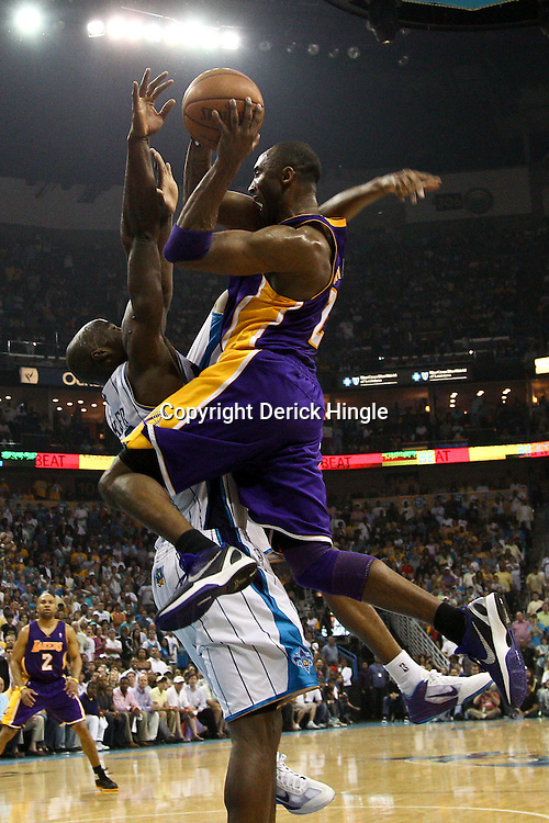 April 24, 2011; New Orleans, LA, USA; Los Angeles Lakers shooting guard Kobe Bryant (24) collides with New Orleans Hornets center Emeka Okafor (50) during the second quarter in game four of the first round of the 2011 NBA playoffs at the New Orleans Arena.    Mandatory Credit: Derick E. Hingle