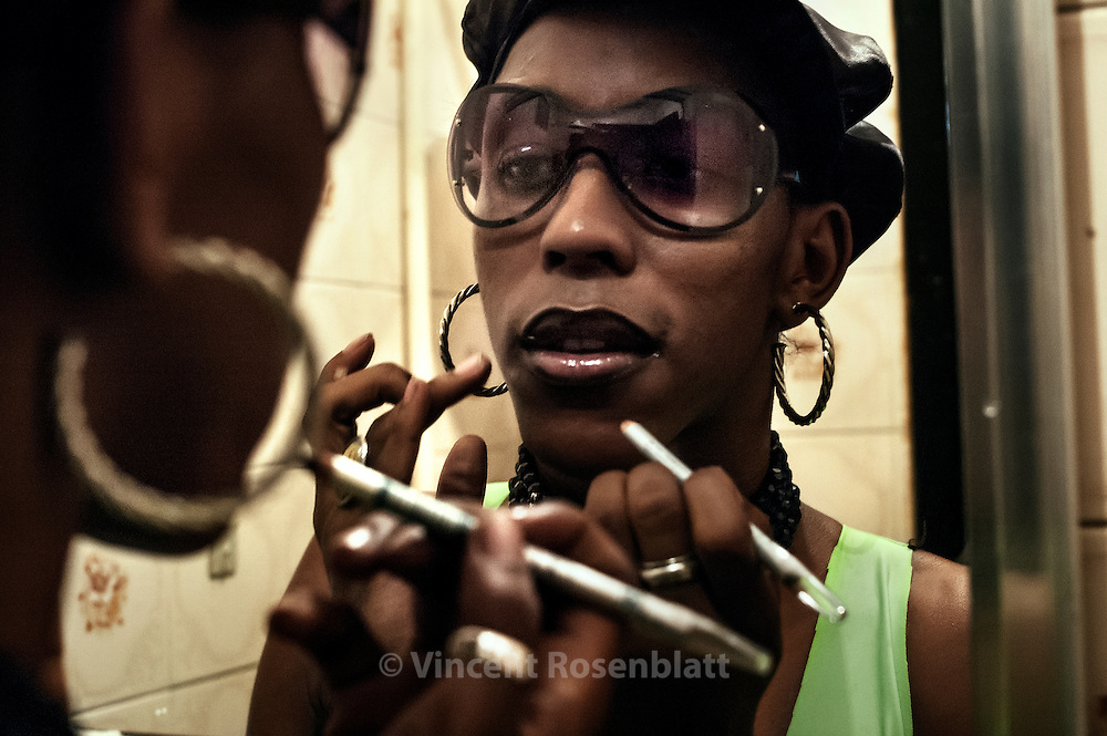 """Lacraia (""""centipede""""), dancer and transvestite, is famous for her duo work with MC Serginho, from the favela Jacarézinho : after years touring bailes Funk, now they present newcomer artists on TV. Lacraia is without doubt the most rapid and supple Funk dancer on the Carioca scene.  Photo: Lacraia putting on her make up before entering the stage at club Nova Show in São Gonçalo."""