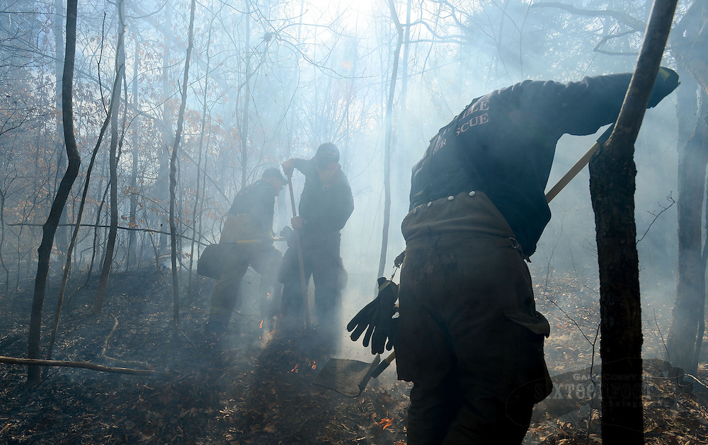 Gary Cosby Jr./Decatur Daily    Firefighters from Hartselle, Flint and the Alabama Forestry Commission fight a fire in Hartselle Thursday.  The Blaze began at a residence in a hollow behind O'Bryans Restaurant and burned up the bluff.