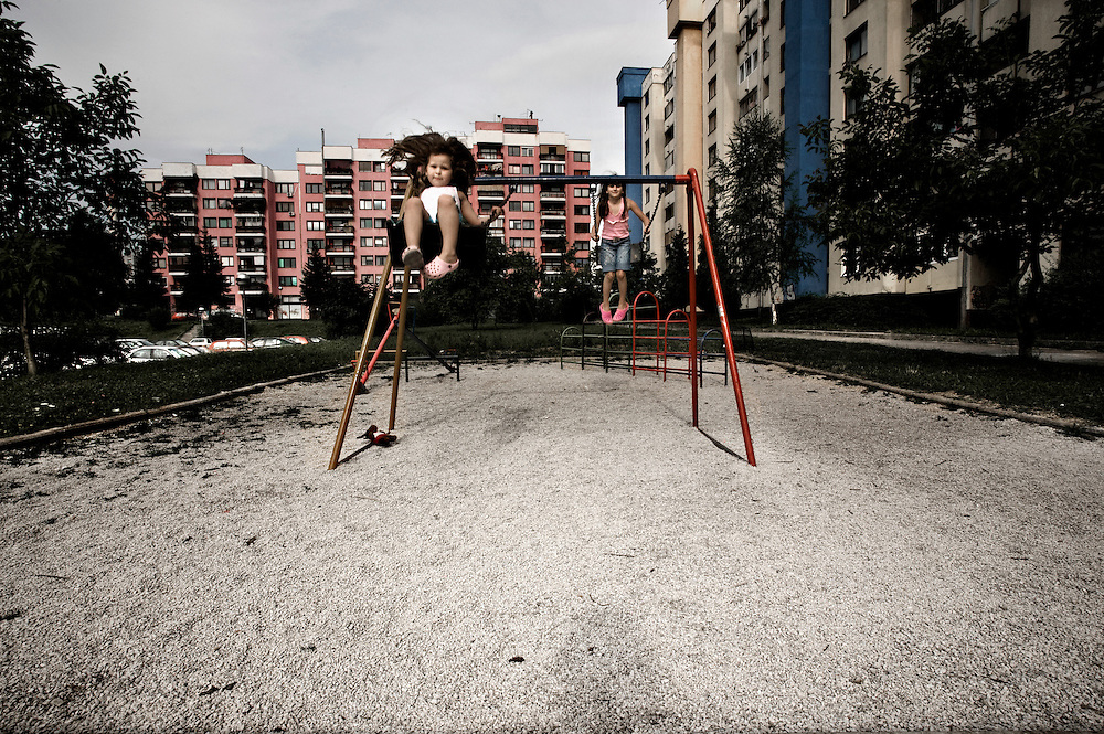 Sarajevo.Two children swing at the Mojmilo's playground. Mojmilo is the Sarajevo's Olympic village built in 1984 close to Dobrinja, Sarajevo's suburb, for the winter Olympic Games. In 1992 during the Balcan war the village has been almost razed to the ground.  One year after the end of war, in 1996 Barcelona's city through some spanish cooperation projects rebuilt a big part of the village. At time in Mojmilo live approximately 4 thousand people, most of them are young couples with children, teenagers and university students.
