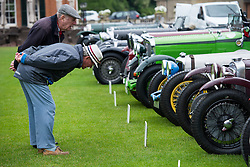 © Licensed to London News Pictures. 13/07/2015. Epsom, UK. Two Classic car enthusiasts examine cars on show before the race. The start of The Royal Automobile Club 1000 Mile Trial 2015 at Woodcote Park in Epsom, Surrey. The event, which starts and finishes at Woodcote Park, takes a fleet of over 40 classic cars from around the world, through a 1000 mile trial around the UK.  Photo credit: Ben Cawthra/LNP