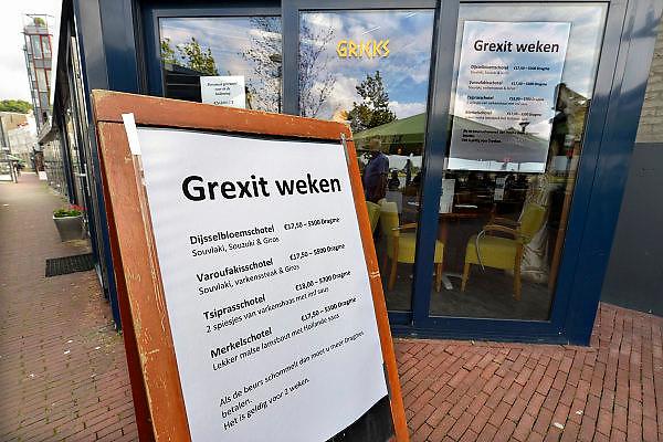 Nederland, Nijmegen, 21-6-2015De eigenaar van een Grieks restaurant aan de Waalkade heeft speciale aanbiedingen n.a.v. de Griekse geldcrisis en een mogelijke Grexit. Dijsselbloemschotel, varoufakisschotel, Tsiprasschotel en Merkelschotel. De prijzen in drachmen staan er al bij...Foto: Flip Franssen