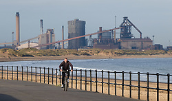 © Licensed to London News Pictures.20/10/15<br /> Redcar, UK. <br /> <br /> A man cycles along the promenade in front of the recently closed SSI UK steel blast furnace in Redcar, England. The closure of the site marks the end of 170 years of steel making heritage on Teesside and was the first of a number of recent closures of steel making plants across the UK.<br /> <br /> Photo credit : Ian Forsyth/LNP