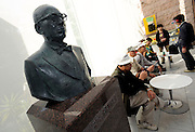 Visitors take a rest next to a bust of instant noodle inventor Momofuku Ando, which stands in the entrance hall of the Momofuku Ando Instant Ramen Museum in Osaka, Japan on 20 October 2008. Ando invented the world's first instant noodles, which he named Chikin Ramen, on August 25, 1958 after hours of research in a shack he constructed in the backyard of his Osaka home. Ando reportedly ate instant noodles every day of his life. The Taiwan-born Ando died in 2007 aged 96..