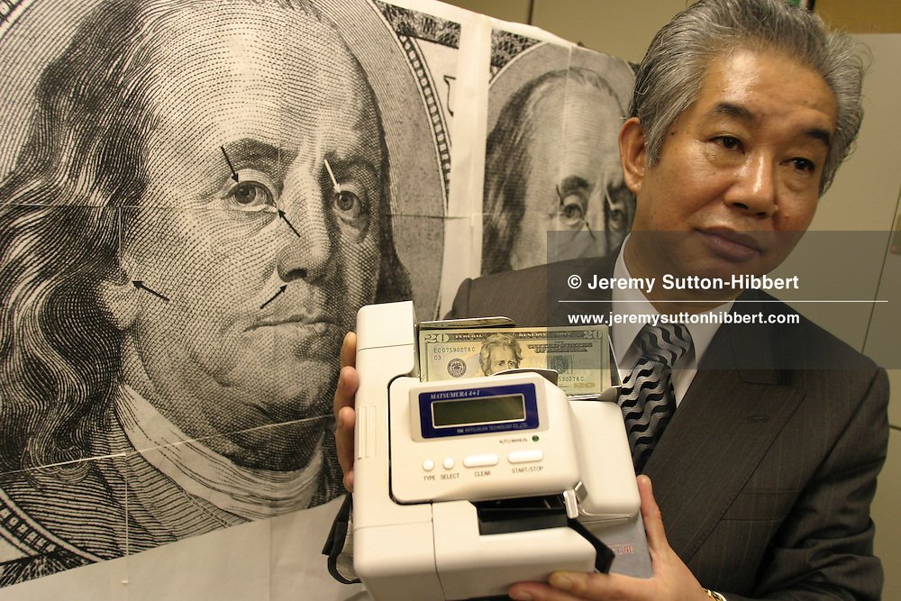 """Yoshihide Matsumura, Director of Matsumura Technology Co. Ltd, a Japanese company specializing in machines to detect counterfeit currencies. Photographed with fake American dollar bank notes, Euros, and Japanese Yen. His 'Matsumura 4 + 1' counterfeit currency detection machine retails for 4,500 USD, and can detect the best fake notes such as the American dollars """"Super K"""", and """"Super Z"""" fakes."""