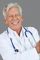 Portrait of happy senior male doctor over gray background
