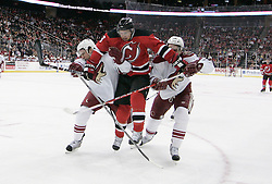 Mar 12, 2009; Newark, NJ, USA; New Jersey Devils left wing Zach Parise (9) jumps between two Phoenix Coyotes players during the second period at the Prudential Center.
