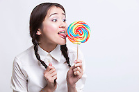 Young Asian woman licking a multicolored lollipop against white background