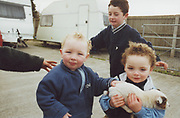 Group of kids, one holding a puppy. Winterbourne Travellers site, Bristol, UK, 1990's