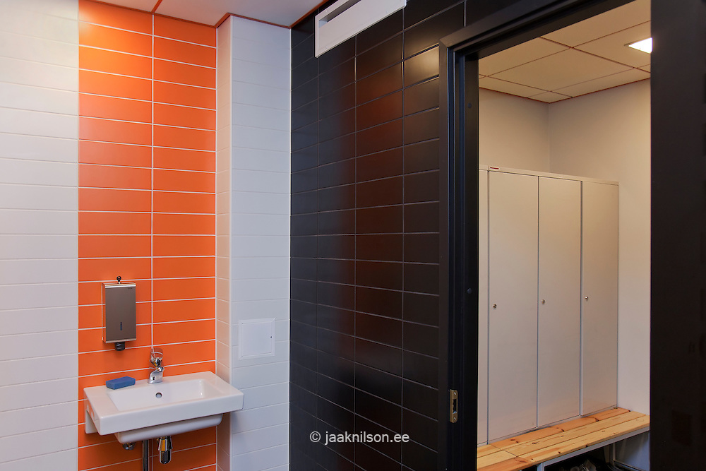 tiled workplace bathroom with sink and lockers