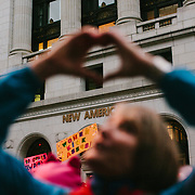 A woman holds up her hands in the form of a heart during the Women's March on Washington