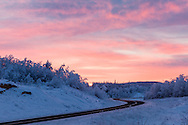 Alpenglow and sunrise along the Alaska Highway somewhere near the border with Canada.  Winter. Morning.