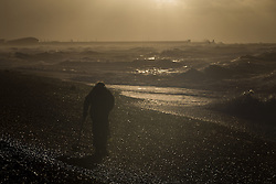 © Licensed to London News Pictures. 27/10/2013. BRIGHTON, UK A man uses a metal detector. Waves at Brighton seafront this morning as Britain was braced for the worst storm for a decade today, which is set to bring driving rain and winds of up to 90mph to some areas. Photo credit : LNP
