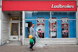 © Licensed to London News Pictures . FILE PICTURE DATED 07/08/2011 . Tottenham , UK . A man carrying three coloured balloons walks by a smashed Ladbrokes betting shop on Tottenham High Road , following a night of rioting . Photo credit : Joel Goodman/LNP