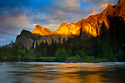 The golden light of sunset reflects off several Yosemite peaks, including the Leaning Tower and Dewey Point, onto the Merced River at Valley View in Yosemite National Park, California. Bridalveil Fall, a 620-foot (189-meter) waterfall, is visible across Bridalveil Meadow on the left side of the image beneath the Cathedral Rocks.